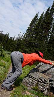 woman wearing red doing a modified downward facing dog called L-Pose in the mountains