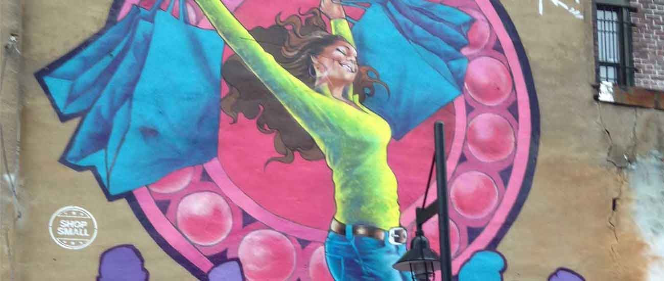 painting on a wall of a woman leaping with joy holding bags
