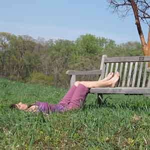 woman wearing purple resting on green grass with her legs on a bench in a restorative yoga pose