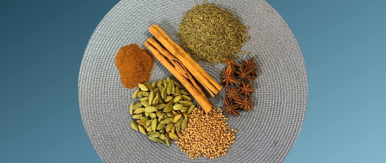 whole spices for chai tea on a blue place mat