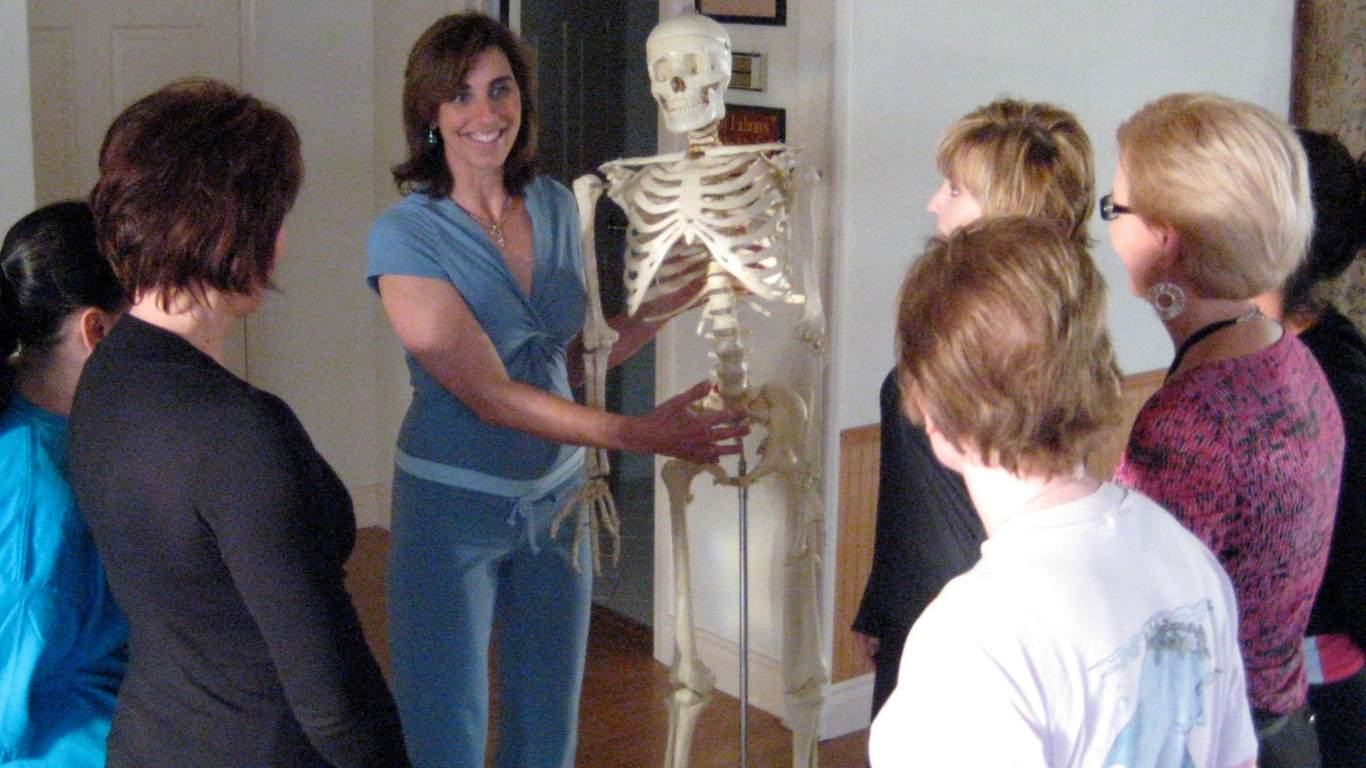 woman wearing blue pointing to a skeleton's pelvis while a group of women listen