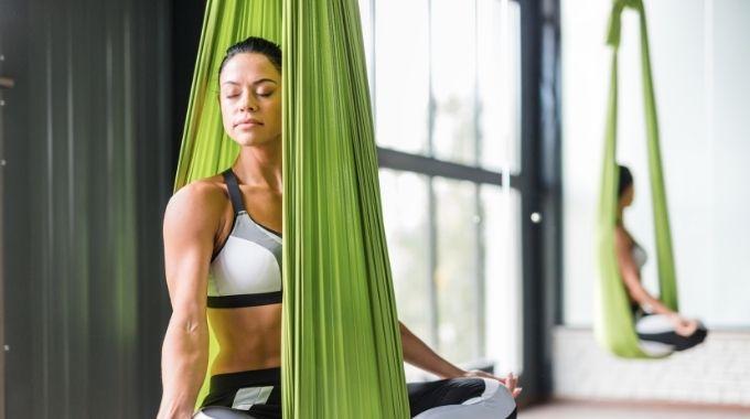 bi-racial woman in green hammock practicing aerial yoga